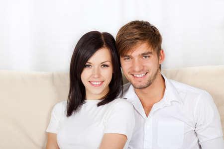 divan: pareja joven hermosa que se sienta en un sof�