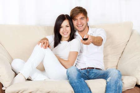 belle jeune couple assis sur un canapé Banque d'images
