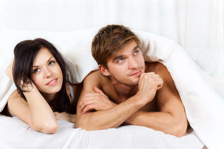 white blanket: young lovely couple lying in a bed, happy smile