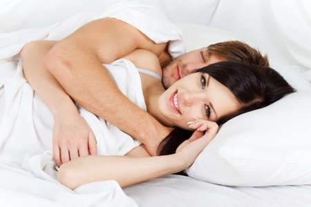 young lovely couple lying in a bed, happy smile photo