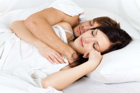young lovely couple lying in a bed, happy sleep photo