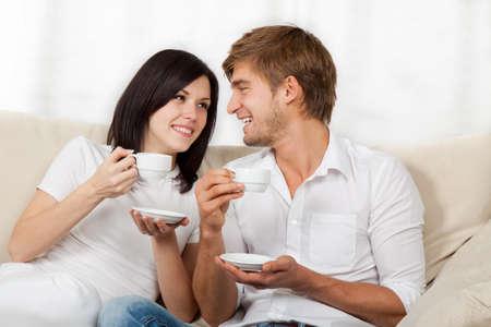 mujer tomando cafe: pareja joven hermosa que se sienta en un sof�