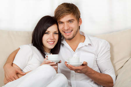 beautiful young couple sitting on a sofa photo