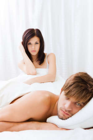 cheating woman: young couple lying in bed problem, conflict Stock Photo