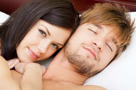 beautiful young happy couple lying in bed photo