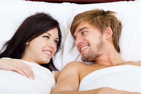 nude in bed: young lovely couple lying in a bed, happy smile
