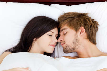 young lovely couple lying in a bed, happy smile