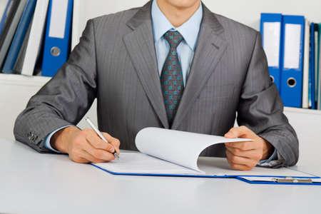 lectura y escritura: Hombre de negocios sentado en el escritorio en la oficina