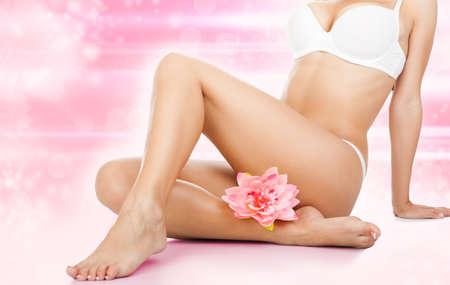 cellulite: Mujer de belleza cuerpo piernas spa cuidado de la piel de cera sobre la flor