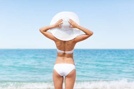 girl ass: Woman on beach, Rear view of young beautiful girl wearing summer hat and bikini, standing back looking to sea blue sky horizon, vacation concept of travel ocean Stock Photo