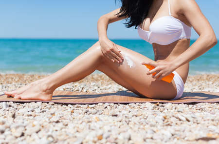 woman apply sunscreen protection lotion hand on hip long legs, young girl with tanned body, sitting on summer beach travel ocean vacation, female applying suntan cream skin care sun protect photo