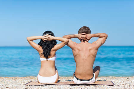 Couple on beach sunbath tanning, rear view sitting back man and woman sea shore, summer ocean vacation holiday blue sky photo