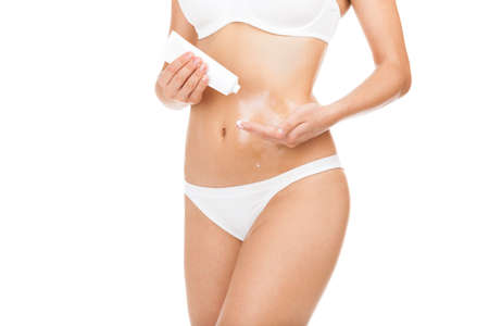 moisturizers: Woman applying moisturizer cream lotion on belly, young girl body care wear panties underwear isolated over white background