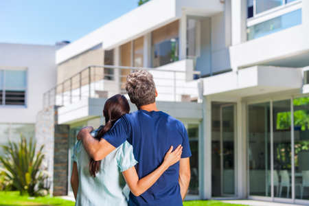 couple embracing in front of new big modern house, outdoor rear view back looking at their dream home Stock Photo