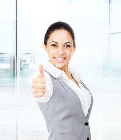 Business woman thumb up gesture, in modern office photo