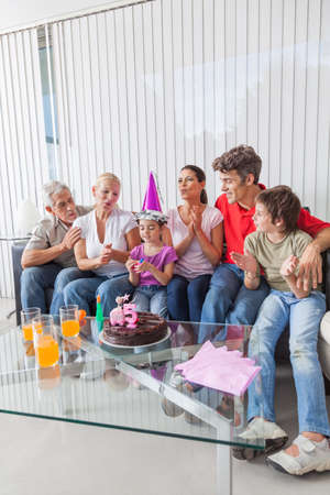 little girl blowing out candles on cake photo