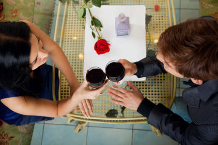 Young happy couple romantic date drink glass of red wine at restaurant photo