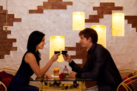 Young happy couple romantic date drink glass of red wine at restaurant Фото со стока