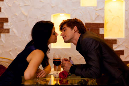 Young happy couple romantic kissing date with glass of red wine at restaurant, celebrating valentine day Stockfoto