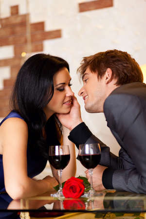Young happy couple romantic kissing date with glass of red wine at restaurant photo