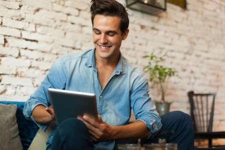 in  shirt: Hombre ocasional que usa la sonrisa de la tableta del ordenador Foto de archivo