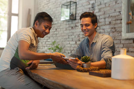 caucasian race: Two Men Using Tablet Computer at Table Cafe, Friends Guys Sitting