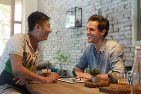 Two Men Sitting at Cafe, Asian Mix Race Friends Guys