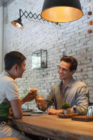 2 つのアイス コーヒーを飲む男性乾杯乾杯、アジア ミックス レース友達