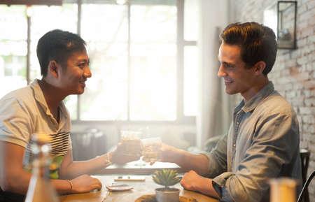 hombres gays: Dos hombres Saludos tostadas bebidas, Asian Mix Race Amigos Chicos Foto de archivo