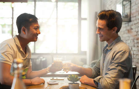 dating: Two Men Cheers Toast Drink, Asian Mix Race Friends Guys Stock Photo