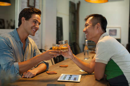 Two Men Cheers Toast Drink Ice Coffee, Asian Mix Race Friends Stock Photo