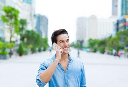 Handsome man cell phone call smile outdoor city street Foto de archivo