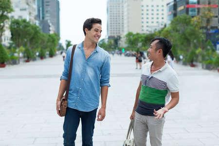 hombres gays: Dos hombres sonrisa hablando al aire libre, amigos mezcla raza asiática Foto de archivo