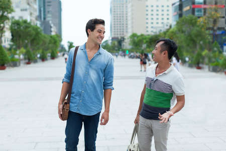 travellers: Two men smile talking outdoor, asian mix race friends
