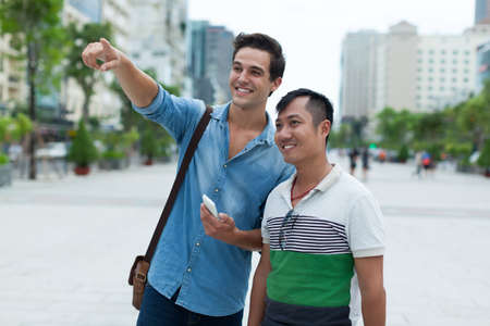 mixed couple: Two men tourists smile point finger sightseeing, asian mix race