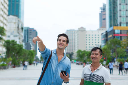 mix race: Two men tourists smile point finger sightseeing, asian mix race