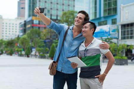 hombres gays: Dos turistas hombres que toman selfie foto sonrisa, mezcla raza asiática