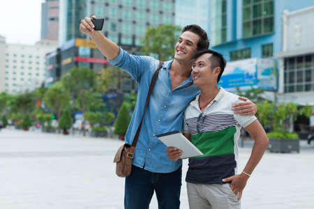 mixed couple: Two men tourists taking selfie photo smile, asian mix race Stock Photo