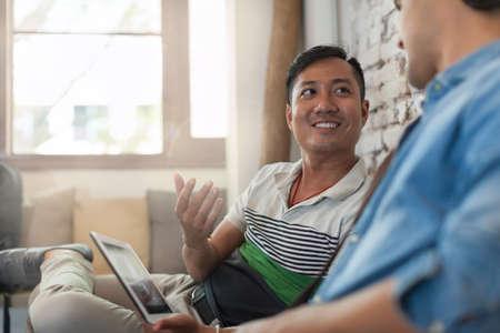 personas dialogando: Dos hombres que usan la computadora portátil en el Café, multiétnicos Amigos Guys Sentado Foto de archivo