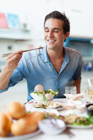Toerist man eten Aziatisch voedsel straat plaatselijke cafe, lachen