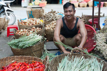 Asian man street market seller bunch green onion photo