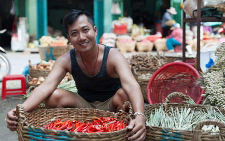 red chilly: Asian man on street market smile sell red chilly pepper Stock Photo