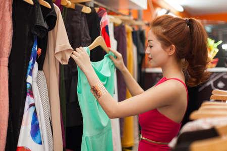 Asian woman shopping choosing trying dress Foto de archivo