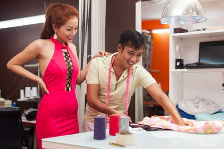 customer tailor: designer asian man tailor shop working on table with woman customer fashion Stock Photo