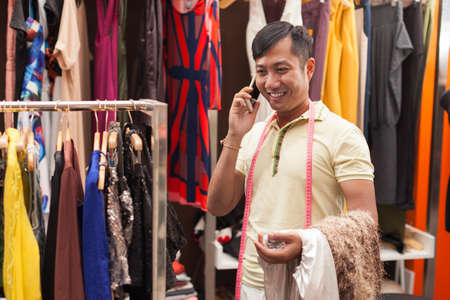 Asian man tailor phone call talking fashion clothes dress photo