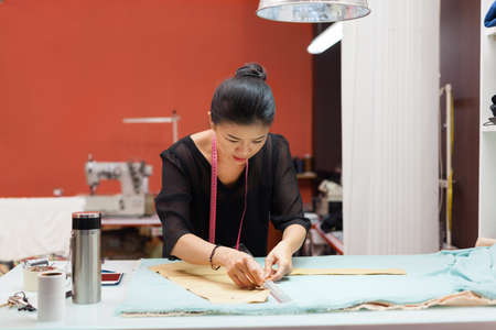 maquinas de coser: Asi�tica de moda mujer ropa sastre dise�ador del vestido de trabajo con la tela Foto de archivo