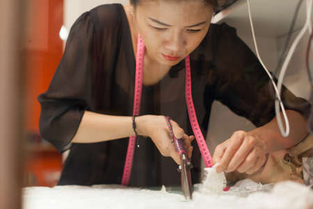 tailor tape: Asian woman tailor fashion clothes dress designer working with scissors fabric
