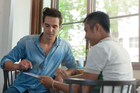 mix race: Two Men Using Tablet, Asian Mix Race Friends Guys Stock Photo