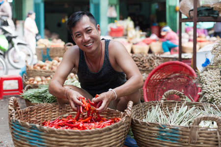 thai chili pepper: Asian man on street market smile sell red chilly pepper Stock Photo
