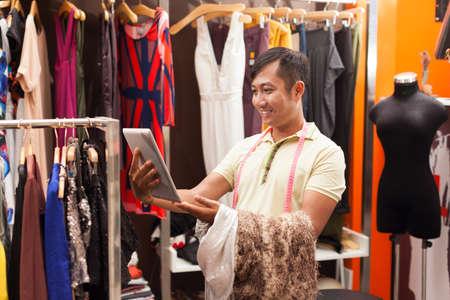 moda ropa: Hombre asi�tico a medida que usa la tableta vestido de ropa de moda equipo
